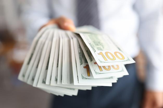 Męska ręka trzyma dużo dolarów w gotówce