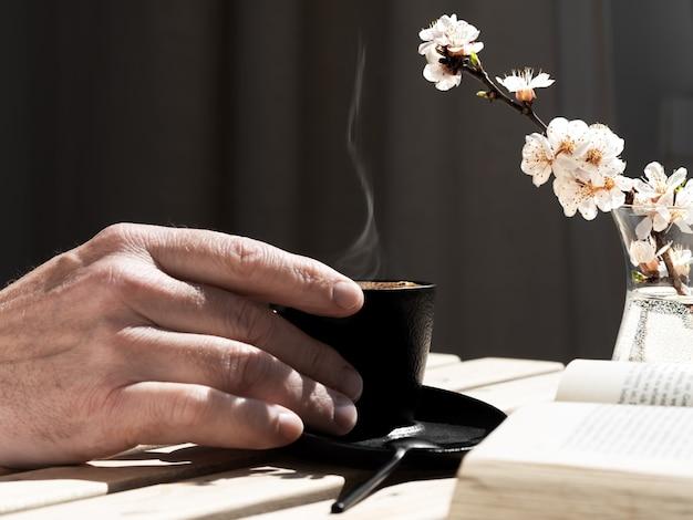 Męska ręka trzyma filiżankę kawy z aromatycznym espresso