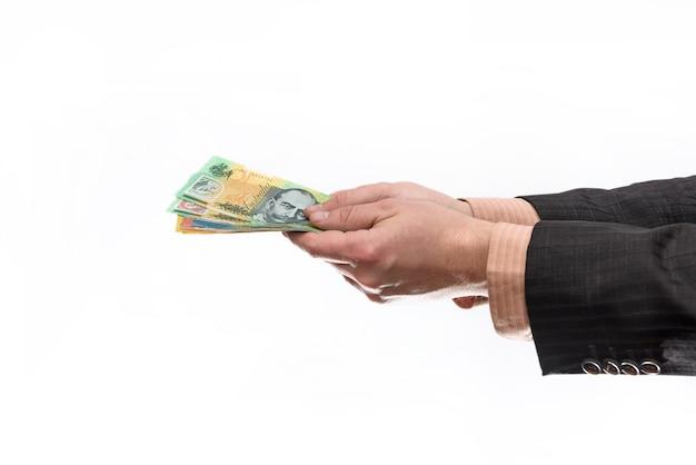 Męska ręka trzyma i oferuje banknoty dolara australijskiego