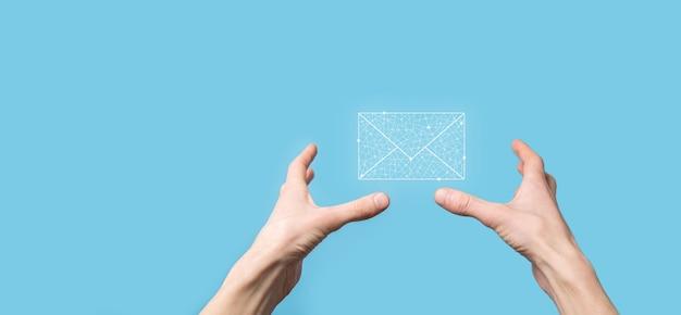 Męska ręka trzyma ikonę listu, ikony e-mail. skontaktuj się z nami przez e-mail biuletyn i chroń swoje dane osobowe przed spamem. centrum obsługi klienta skontaktuj się z nami. marketing e-mail i newsletter.