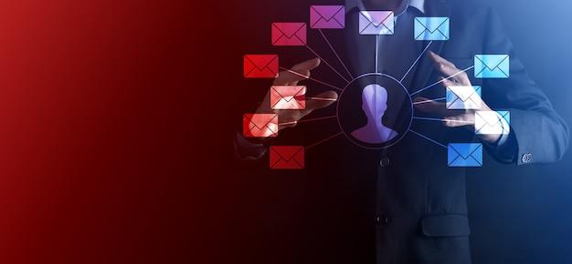 Męska ręka trzyma ikonę listu, ikony e-mail. skontaktuj się z nami przez e-mail biuletyn i chroń swoje dane osobowe przed spamem. centrum obsługi klienta skontaktuj się z nami. marketing e-mailowy i newsletter