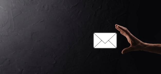 Męska ręka trzyma ikonę listu, ikony e-mail. skontaktuj się z nami przez e-mail z biuletynem i chroń swój osobisty