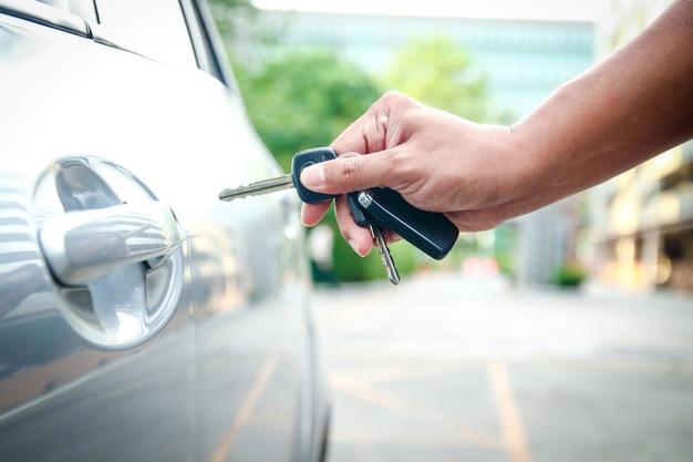 Męska ręka trzyma klucz, aby odblokować drzwi i otworzyć samochód.