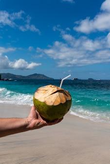 Męska ręka trzyma kokosowe świeże koktajle kokosowe na pięknej plaży w słoneczny dzień.