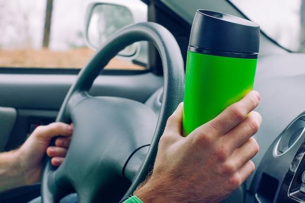 Męska ręka trzyma kubek termiczny z kawą