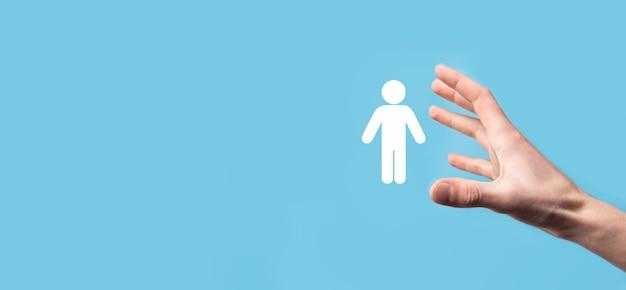 Męska ręka trzyma ludzką ikonę na niebieskiej powierzchni