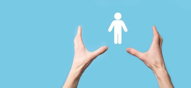 Męska ręka trzyma ludzką ikonę na niebieskim tle. zasoby ludzkie zarządzanie kadrami rekrutacja zatrudnienie headhunting concept.select team leader concept. męską ręką kliknij ikonę człowieka. baner, skopiuj spase.