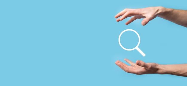 Męska ręka trzyma lupę, ikona wyszukiwania na niebieskiej powierzchni. koncepcja optymalizacji pod kątem wyszukiwarek, obsługa klienta