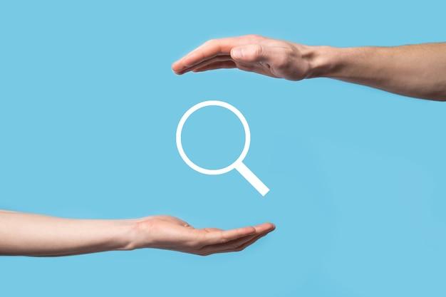 Męska ręka trzyma lupę, ikona wyszukiwania na niebieskiej powierzchni.