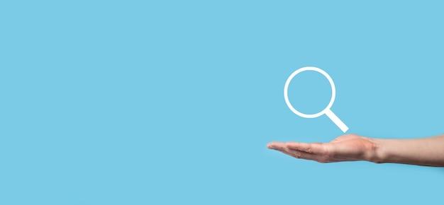 Męska ręka trzyma lupę, ikona wyszukiwania na niebieskiej powierzchni