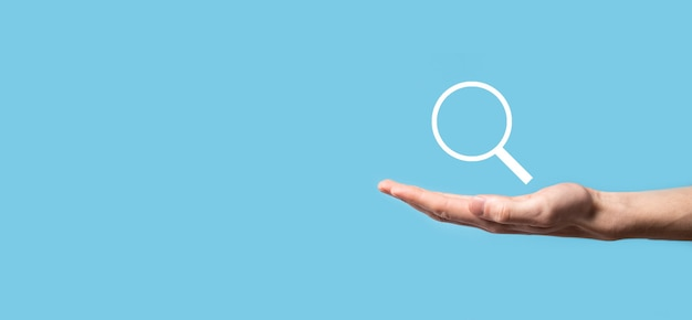 Męska ręka trzyma lupę, ikona wyszukiwania na niebieskim tle.