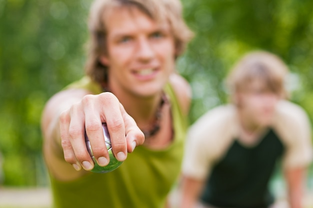 Męska ręka trzyma metalową kulkę