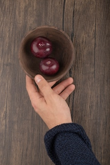 Męska ręka trzyma miskę soczystych śliwek na powierzchni drewnianych