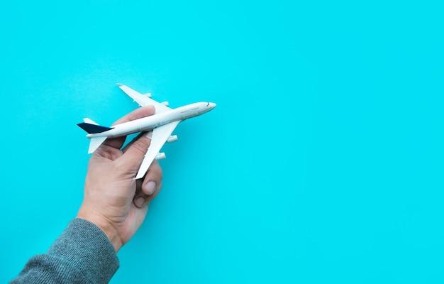 Męska ręka trzyma model samolotu, samolot na niebieskim tle pastelowych kolorów.