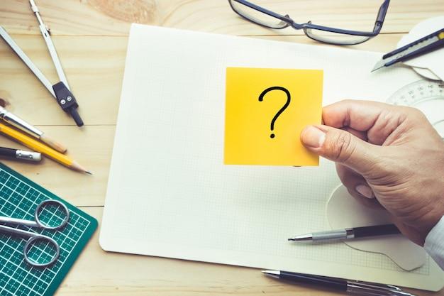 Męska ręka trzyma notatnik ze znakami zapytania na stole roboczym z elementami narzędzi, sprzętu