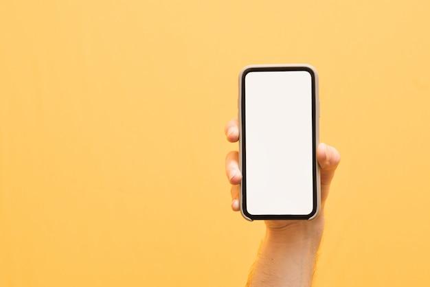 Męska ręka trzyma nowoczesny smartfon z białym, pustym ekranem na żółtym