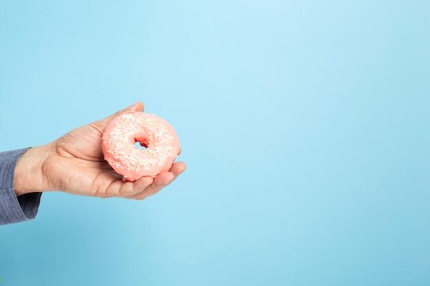Męska ręka trzyma pączka z różowym lukrem i polewą kokosową, niebieskie tło.