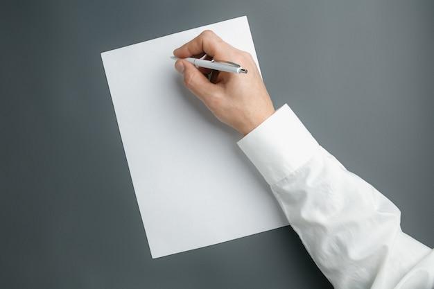 Męska ręka trzyma pióro i pisze na pustym arkuszu na szarej ścianie dla tekstu lub projektu. puste szablony do kontaktu, reklamy lub wykorzystania w biznesie. finanse, biuro, zakupy. copyspace.