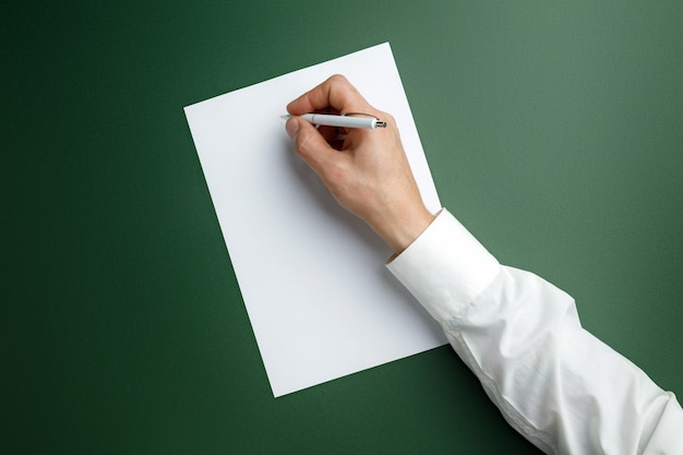 Męska ręka trzyma pióro i pisze na pustym arkuszu na zielonej ścianie tekstu lub projektu. puste szablony do kontaktu, reklamy lub wykorzystania w biznesie. finanse, biuro, zakupy. copyspace.