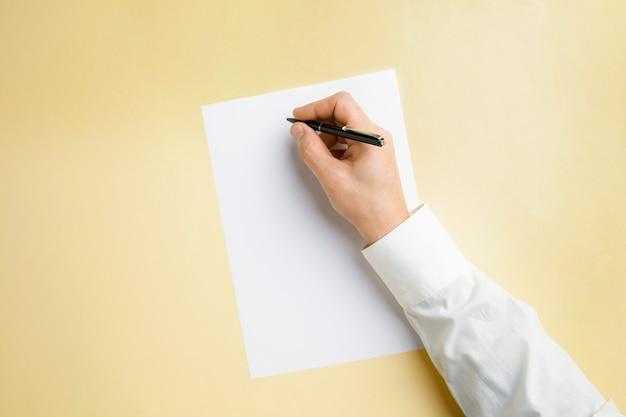Męska ręka trzyma pióro i pisze na pustym arkuszu na żółtej ścianie tekstu lub projektu. puste szablony do kontaktu, reklamy lub wykorzystania w biznesie. finanse, biuro, zakupy. copyspace.