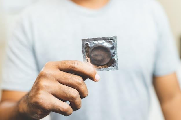 Męska ręka trzyma prezerwatywę. koncepcja bezpiecznego seksu.