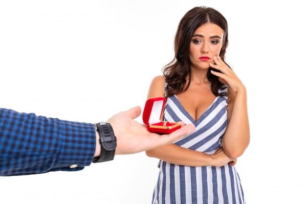 Męska ręka trzyma pudełko z pierścionkiem zaręczynowym i urocza dziewczyna w sukience z dekoltem myśli, co powiedzieć na białej ścianie