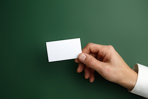 Męska ręka trzyma pustą wizytówkę na zielonej ścianie dla tekstu lub projektu. puste szablony kart kredytowych do kontaktu lub wykorzystania w biznesie. biuro finansów. copyspace.