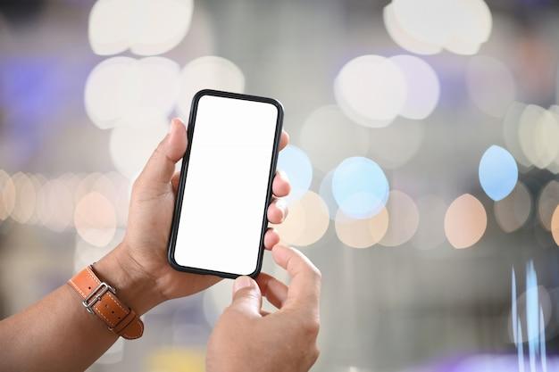 Męska ręka trzyma pustego ekranu telefon komórkowego nad nocy ulicy bokeh.