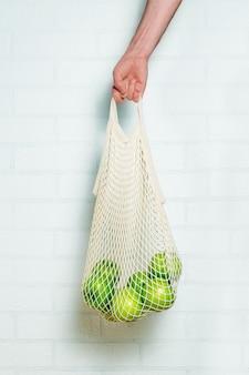 Męska ręka trzyma siatkową torbę na zakupy na białym murem