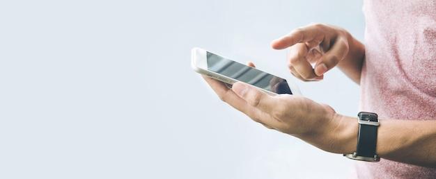 Męska ręka trzyma smartfon, mobilny z miejsca na kopię na tle rozmiaru banera.