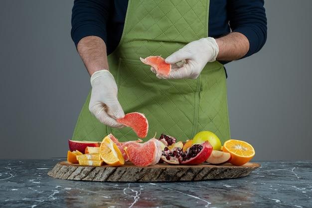 Męska ręka trzyma soczysty grejpfrut na marmurowym stole.
