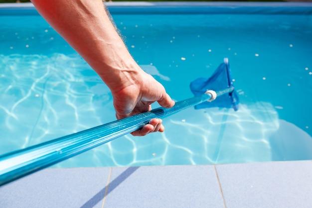 Męska ręka trzyma środek czyszczący do basenu