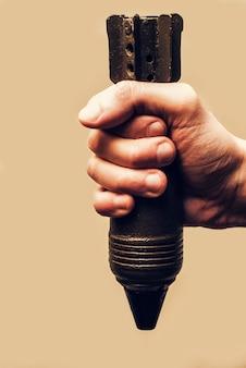 Męska ręka trzyma starą rdzewiejącą moździerzową ii wojny światowej. koncepcja wojny