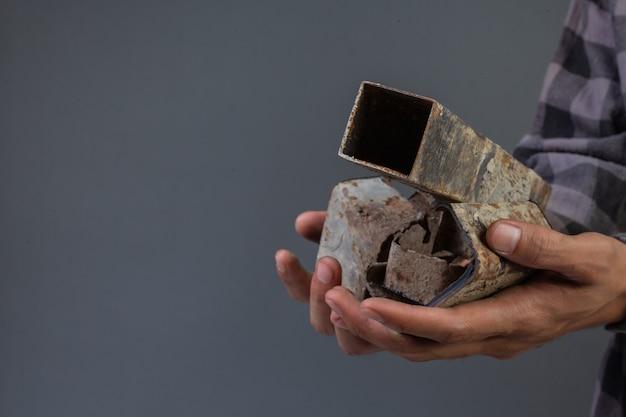 Męska ręka trzyma stary złom żelazny z szarym.