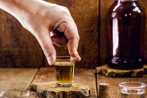 Męska ręka trzyma szklankę destylowanego napoju alkoholowego, zwanego w brazylii