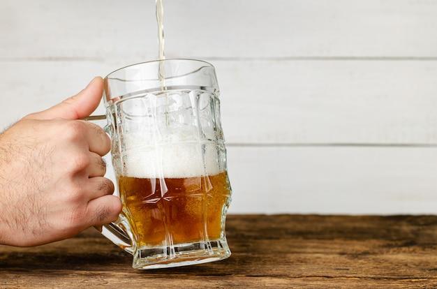 Męska ręka trzyma szkło i nalewa piwo.