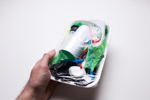 Męska ręka trzyma tacę z odpadami z tworzywa sztucznego