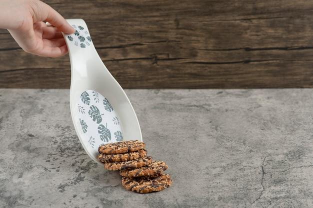 Męska ręka trzyma talerz herbatników z sezamem na marmurze.