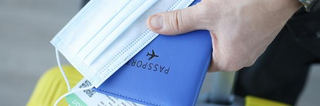 Męska ręka trzyma walizkę i maskę ochronną z paszportem szczepień zbliżeniem podróżowanie