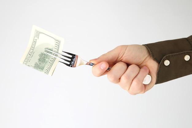 Męska ręka trzyma widelec z pieniędzmi