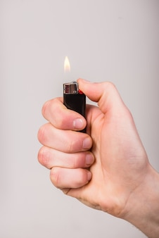 Męska ręka trzyma zapalniczkę