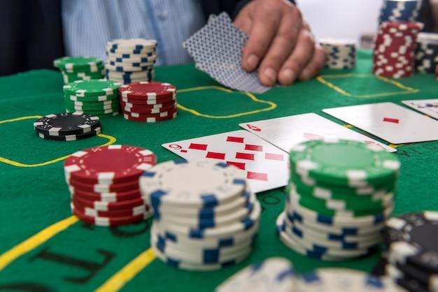 Męska ręka trzyma żetony i karty do pokera na stole w kasynie. gaming biznes, koncepcja sukcesu