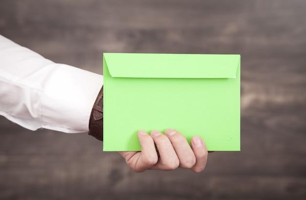 Męska ręka trzyma zieloną kopertę pocztową.