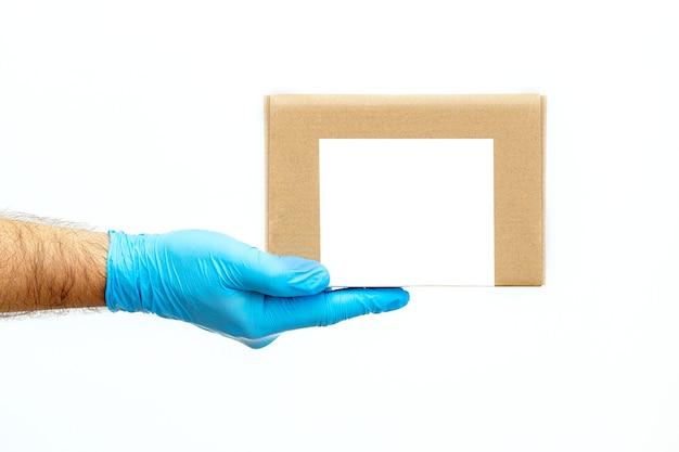 Męska ręka trzymająca kartony w rękawiczkach medycznych. skopiuj miejsce. szybki i darmowy transport dostawy. zakupy online i ekspresowa dostawa.