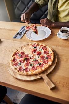 Męska ręka trzymająca kawałek pizzy, podczas gdy pan siedzi przy stole z filiżanką kawy w stołówce in