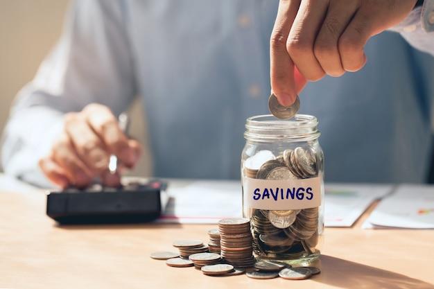 Męska ręka trzymająca monety wkładająca szkło, oszczędzająca pieniądze i inwestująca koncepcja oszczędzająca pieniądze na księgowość finansową