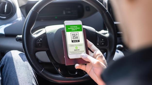 Męska ręka trzymająca paszport i smartfon z kodem qr międzynarodowego świadectwa szczepień covid-19 w samochodzie