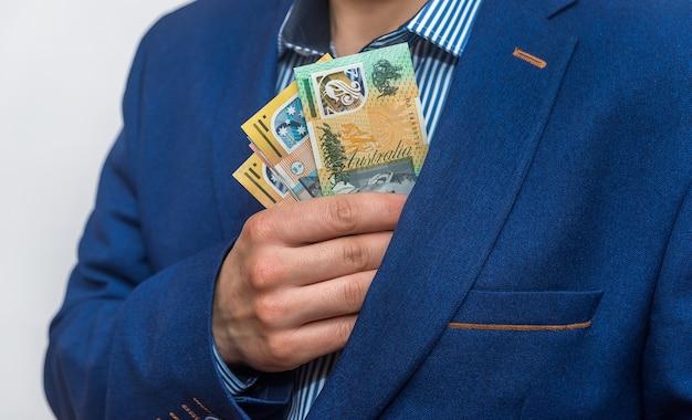 Męska ręka ukrywa banknoty dolara australijskiego w kieszeni