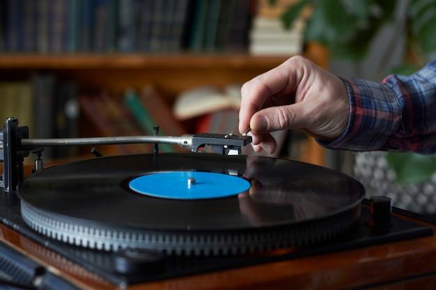 Męska ręka umieszcza igłę na rekordowej płycie
