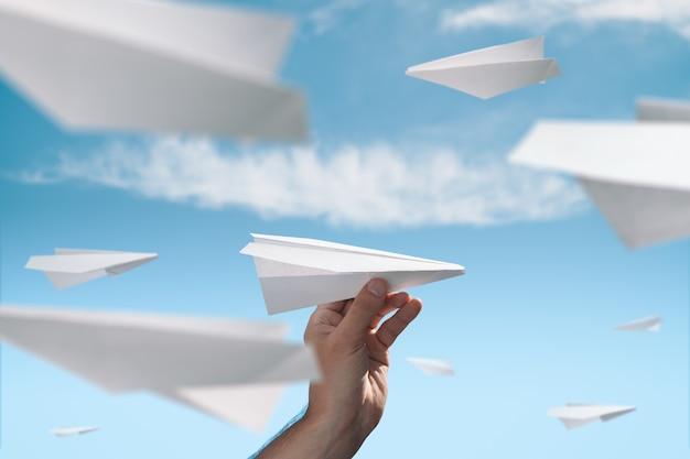 Męska ręka uruchamia papierowy samolot